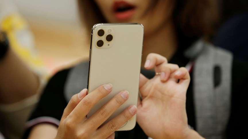 Uma mulher segura seu iPhone 11 Pro Max na China: decisão do STF pode baratear celulares importados