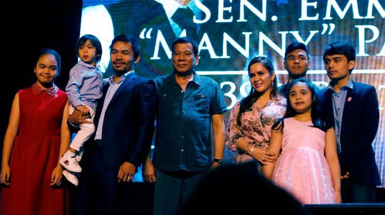 O boxeador Manny Pacquiao (segundo à esquerda) é visto com o presidente Rodrigo Duterte e sua família quando ele comemora seu 39º aniversário em dezembro de 2017