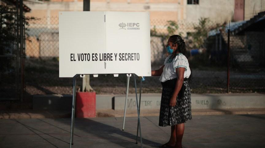 Mesária desinfecta estação de votação em Atzacoaloya, no estado mexicano de Guerrero