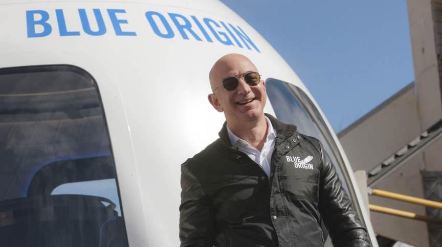 O bilionário Jeff Bezos em frente ao foguete de sua empresa de viagens espaciais, a Blue Origin