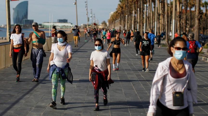Pessoas caminham, se exercitam e tomam sol na orla em Barcelona, na Espanha, neste sábado