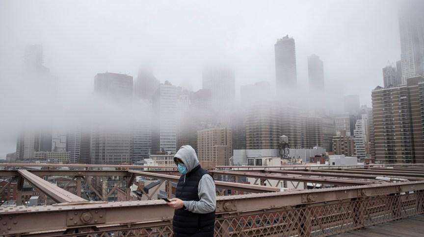 Homem de máscara caminha na ponte do Brooklin, em Nova York (EUA), durante a pandemia de COVID-19 , em março de 2020