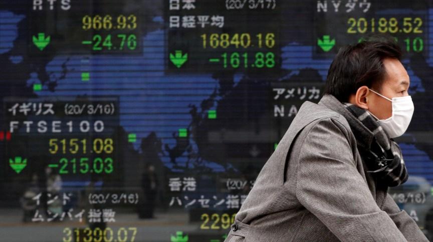 O homem passa à frente da Bolsa de Tóquio (17.mar.2020)