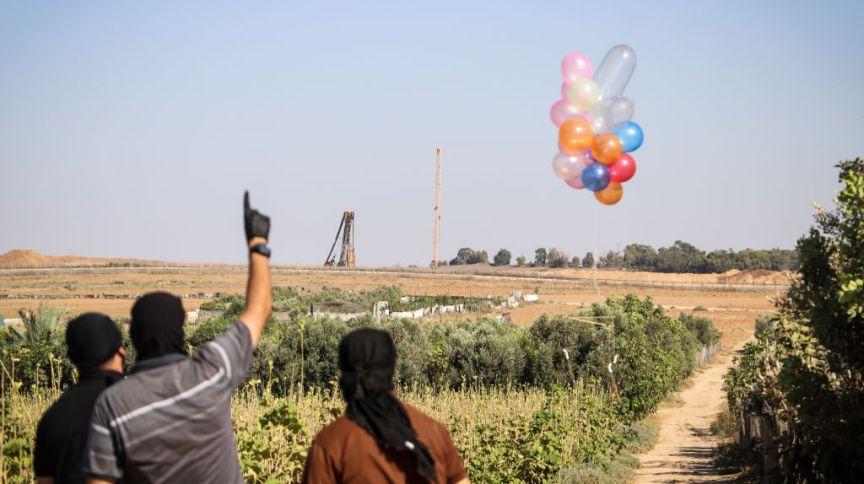 Palestinos mascarados soltando balões com artefatos incendiários ao longo da fronteira entre Israel e Gaza