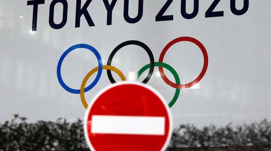 Logo da Olimpíada ao lado da placa de trânsito em Tóquio