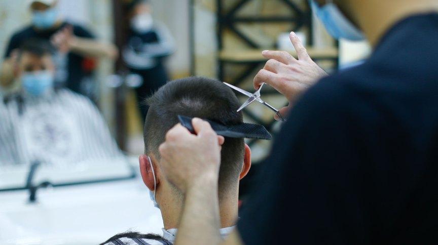 Cabeleireiro e cliente usam máscaras durante atendimento.