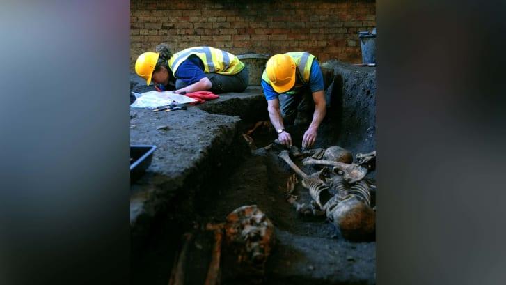 Membros da Unidade Arqueológica de Cambridge escavam esqueletos em 2010