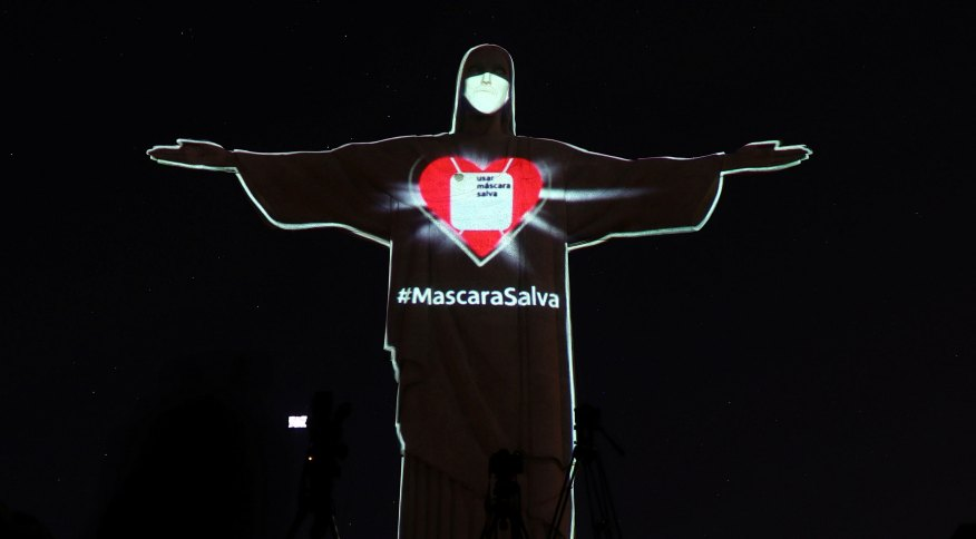 """O Cristo Redentor, no Rio de Janeiro, iluminado com uma máscara sobre o rosto e a inscrição """"Usar máscara salva"""" sobre o peito"""