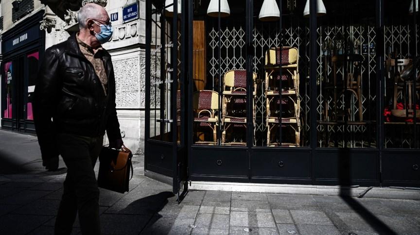 Homem passa por restaurante fechado em Paris; estudo aponta que primeiro caso de Covid-19 na França pode ter sido em dezembro