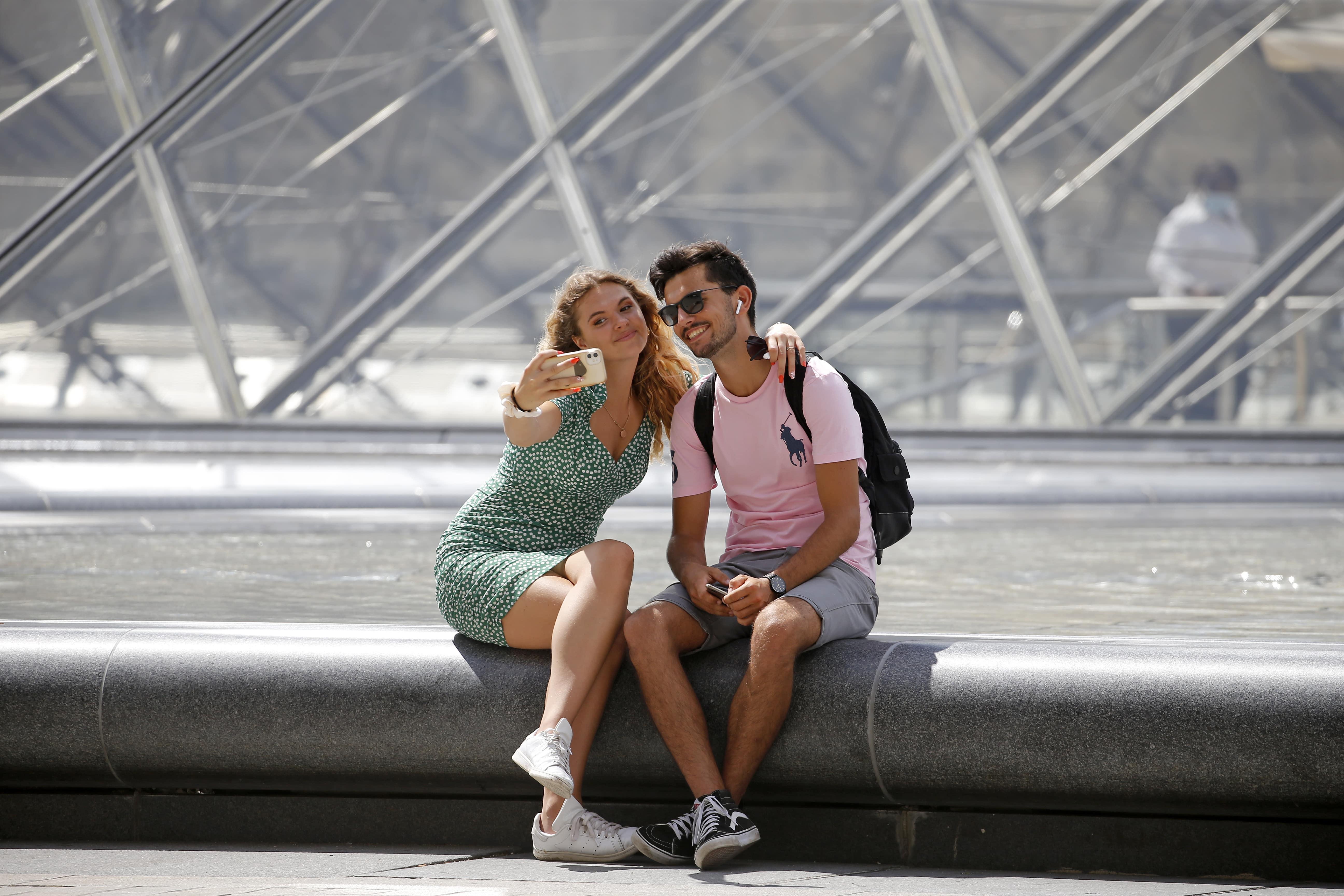 Turistas tiram foto em frente à pirâmide do Louvre