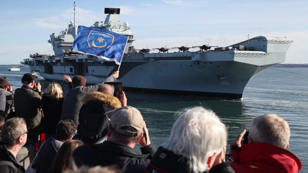 O porta-aviões britânico HMS Queen Elizabeth é saudado ao chegar à Base Naval