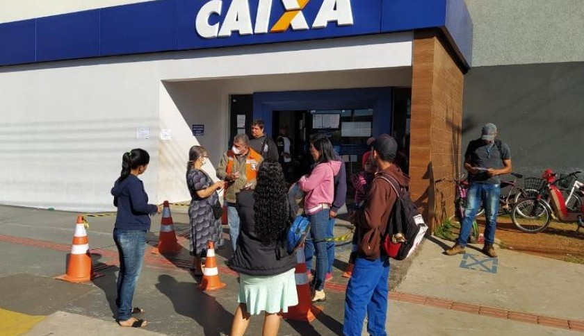 Funcionário da Caixa Econômica auxilia pessoas interessadas na retirada do auxílio emergencial