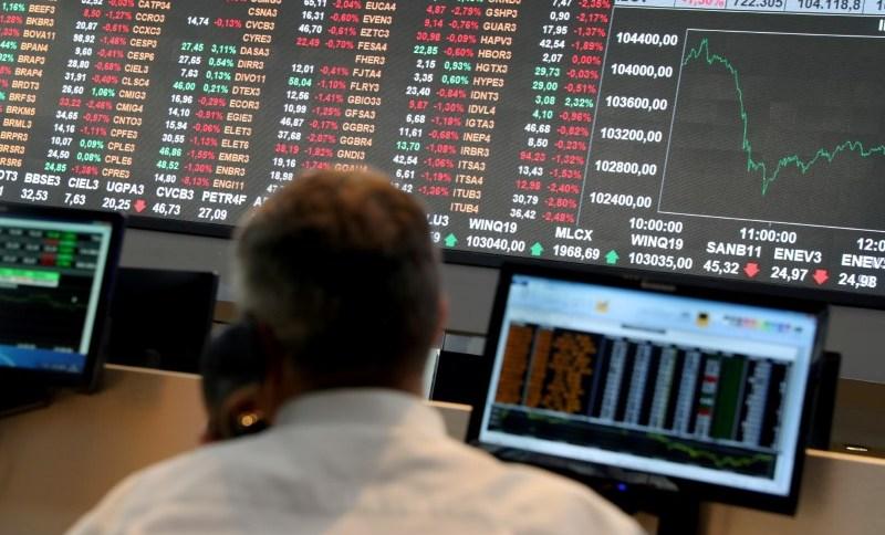 Operador olha para quadro eletrônico com índices da Bolsa de Valores de São Paulo