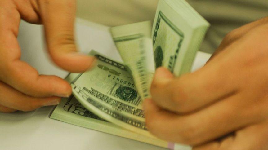 Pessoa contando dólares: moeda americana pressiona o real