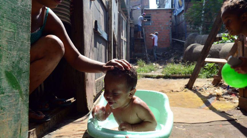 Bebê toma banho em favela