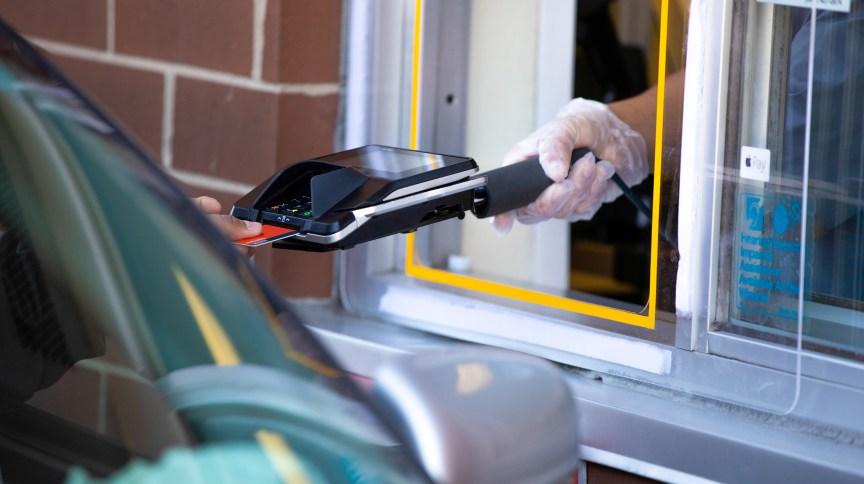 Funcionária do McDonald's utiliza equipamento especial de distanciamento e luvas para receber pagamento de cliente nos Estados Unidos