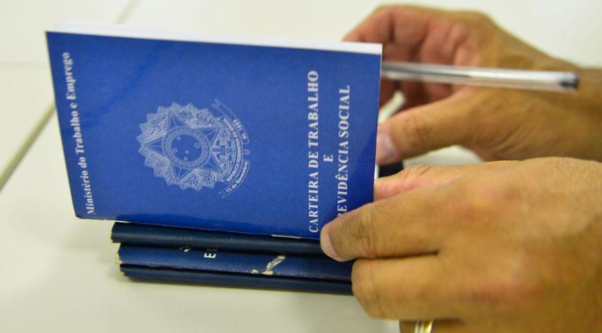 Homem folheia carteira de trabalho: contratos poderão ser suspensos por quatro meses