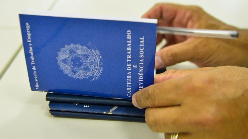 Homem folheia carteira de trabalho: nova MP permite suspensão do contrato por 4 meses