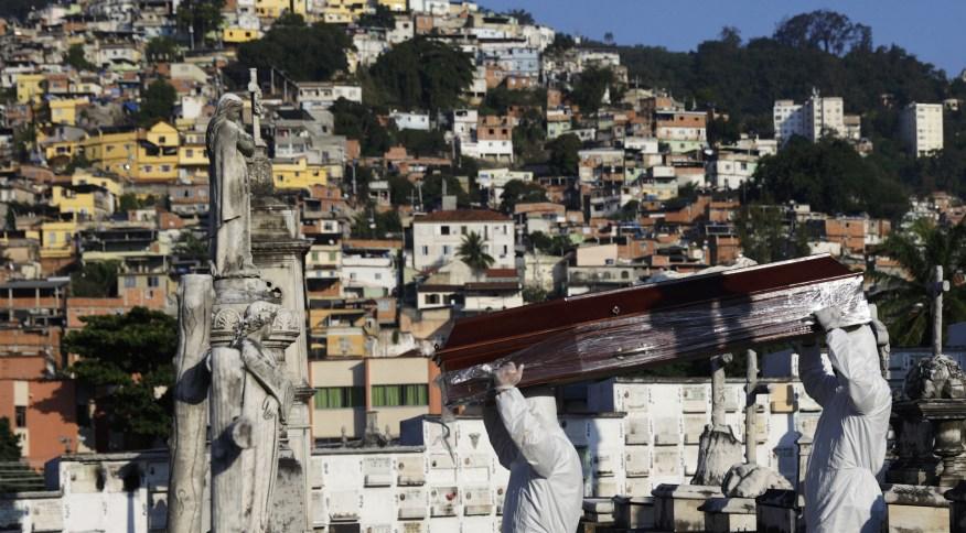 Coveiros com roupas de proteção carregam caixão no Rio de Janeiro