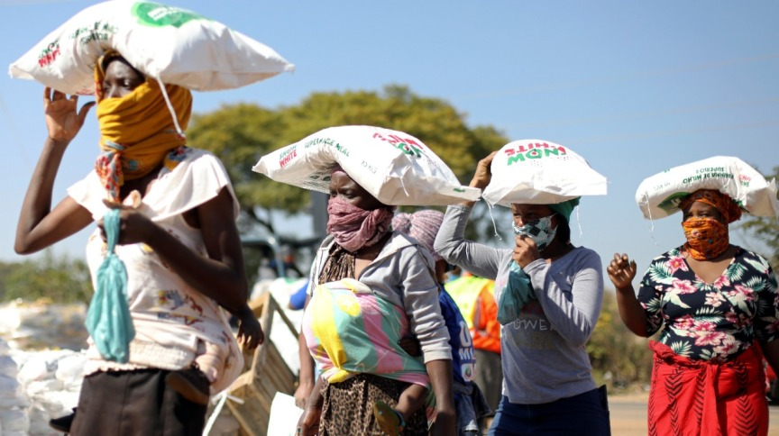 Mulheres carregam saco de milho recebido de doação em Pretória, na África do Sul