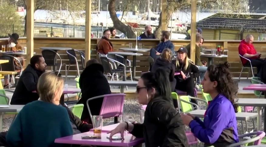 Pessoas conversam do lado de fora de uma cafeteria em Estocolmo
