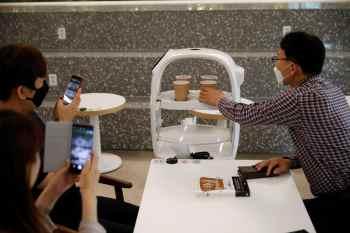 O sistema, que usa um braço robótico para fazer café e um robô para servir, pode fazer 60 tipos de café e serve as bebidas para os clientes em seus assentos