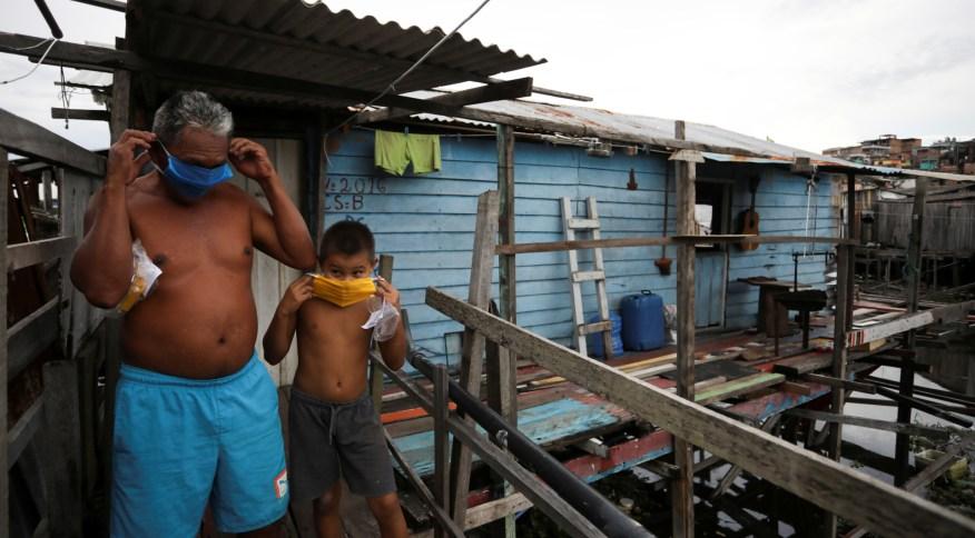 Moradores de comunidade de Manaus colocam máscara para evitar contaminação pelo novo coronavírus