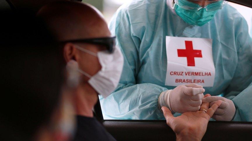 Profissional da Cruz Vermelha tira amostra para teste de Covid-19 em frente ao estádio Mané Garrincha, em Brasília