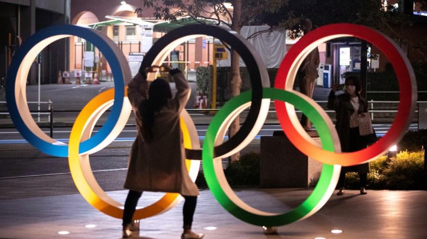 Mulheres com máscara de proteção tiram foto com símbolo olímpico em Tóquio: jogos foram adiados