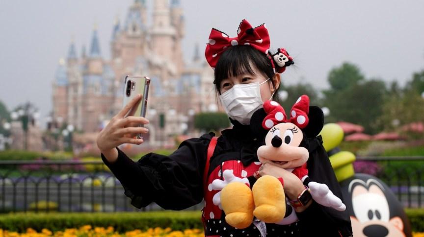 Visitante de parque da Disney tira selfie usando máscara de proteção. (11/5/2020)