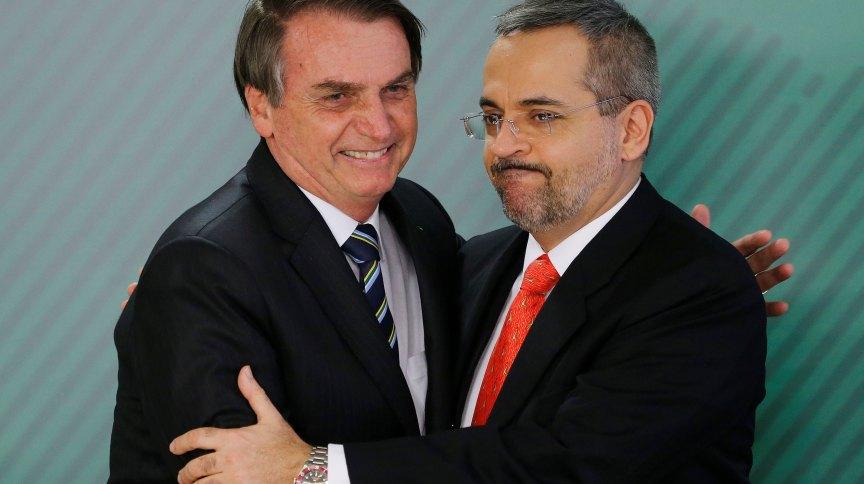 O presidente Jair Bolsonaro e o ministro da Educação Abraham Weintraub se abraçam em cerimônia no Palácio do Planalto
