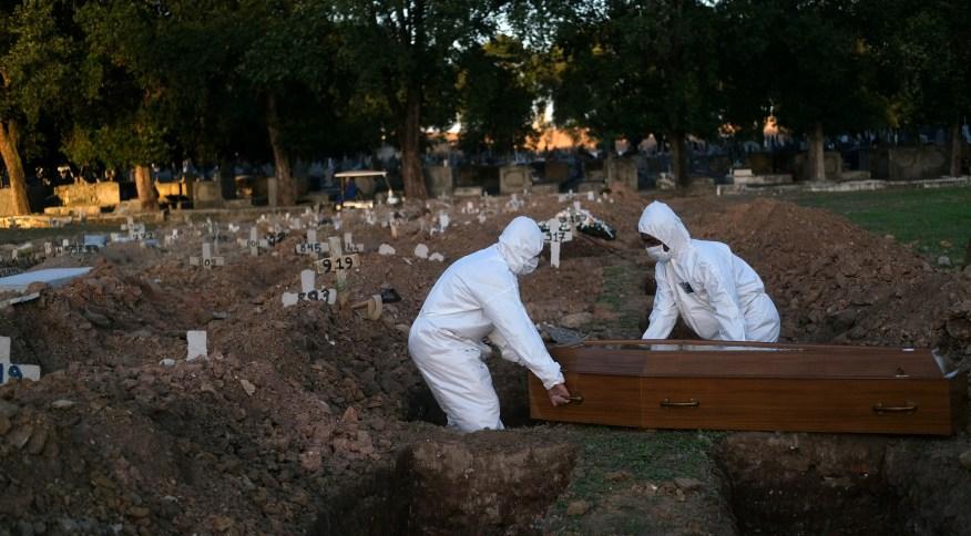 Coveiros sepultam pessoa que morreu infectada pelo novo coronavírus em cemitério do Rio de Janeiro