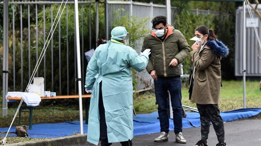 Enfermeiro conversa com casal em ponto de checagem médica em hospital em Brescia, na Itália