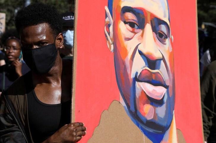 Manifestante segura cartaz com rosto de George Floyd durante protesto em Nova York
