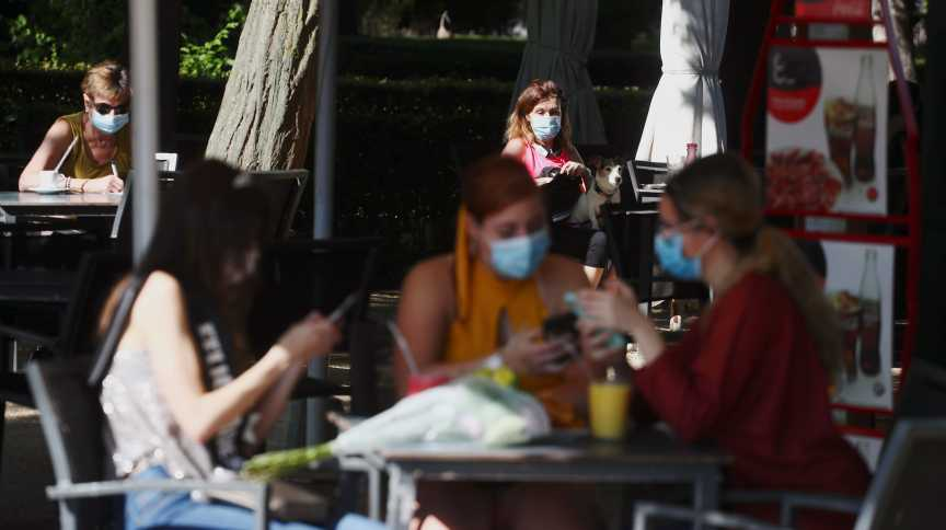 Pessoas com máscara de proteção sentam em mesas de quiosque no Parque del Retiro, em Madrid