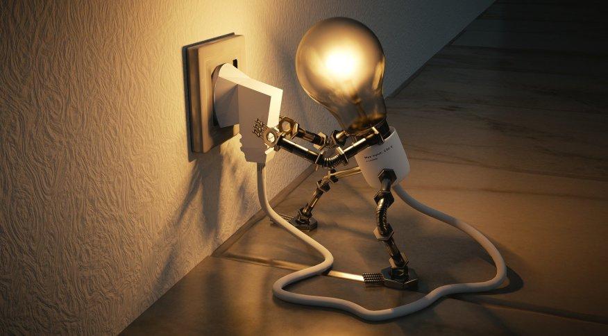 Lâmpada acesa em residência; energia gerada por concessionárias