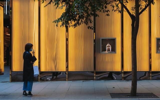 Mulher baixa máscara para fumar em frente a uma loja durante a quarentena durante pandemia de coronavírus, na Austrália
