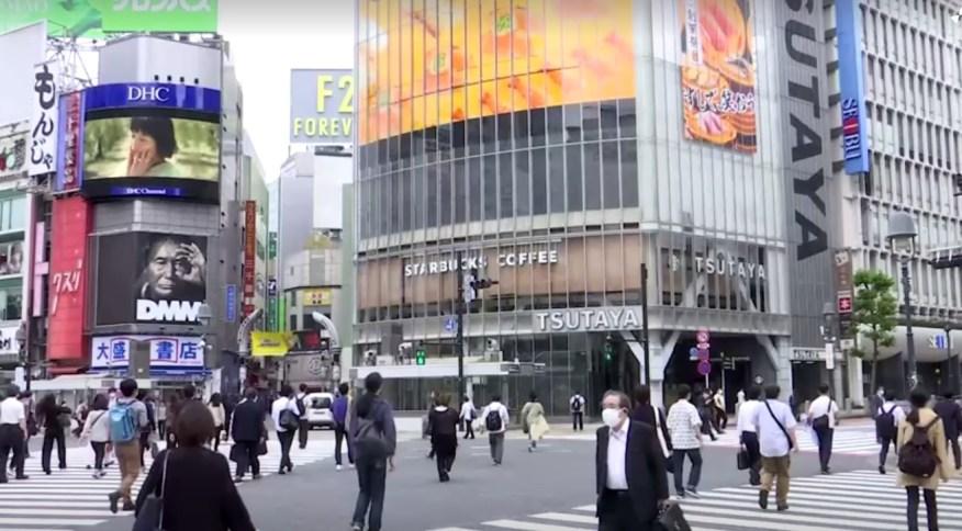 Japoneses caminham no cruzamento de Shibuya, em Tóquio