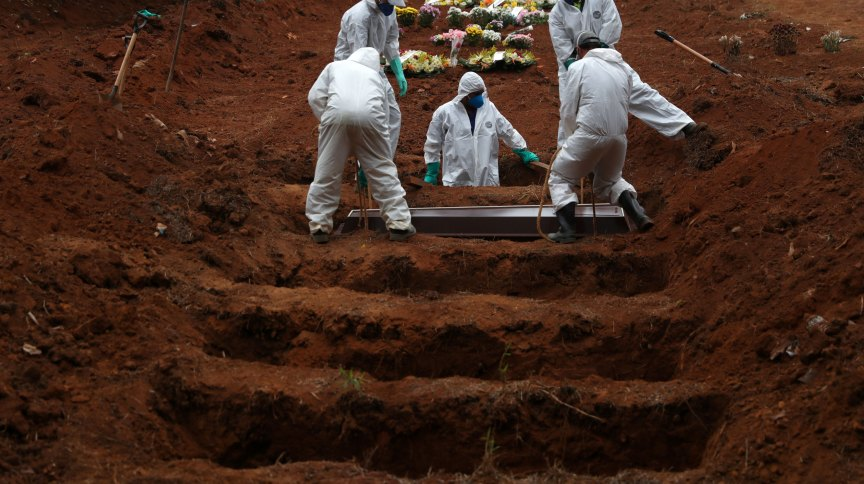 Coveiros em roupas de proteção enterram vítima da Covid-19 no cemitério São Luiz, em São Paulo