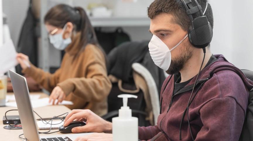 Pessoas trabalhando em um escritório usando máscaras respiratórias.