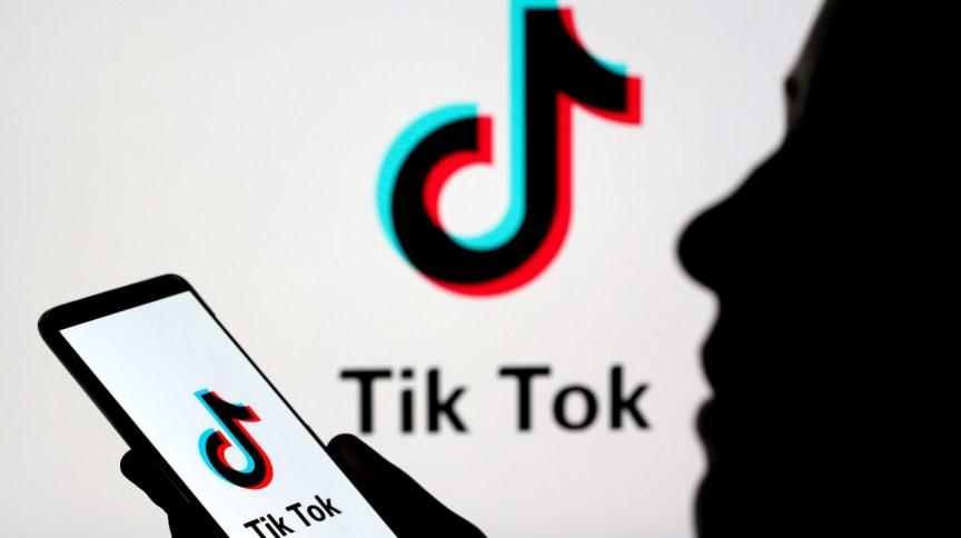 Jovem manipula smartphone com logotipo da TikTok