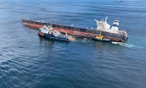O navio Stellar Banner, encalhado na costa do Maranhão, e uma embarcação especializada para retirar óleo