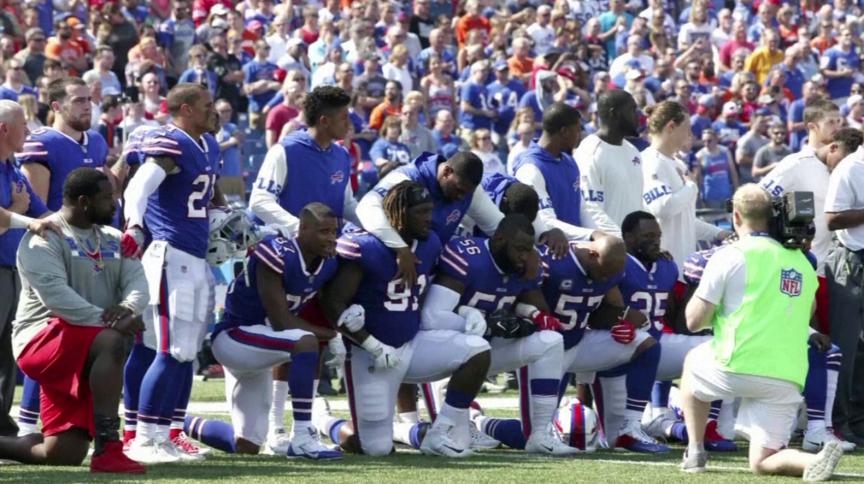 Jogadores do Buffalo Bills se ajoelham durante o hino dos EUA em partida contra o Denver Broncos em setembro de 2017; liga planeja tocar música considerada 'hino nacional negro'