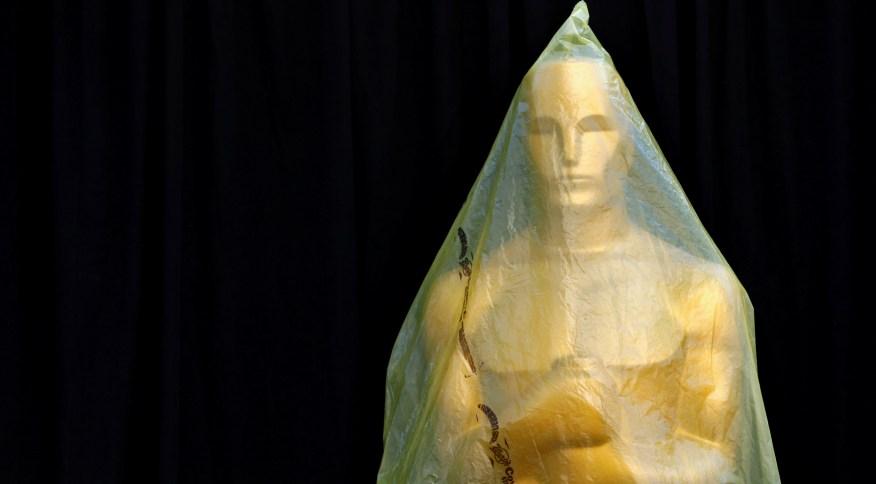 Estátua do Oscar coberta em plástico durante preparativos para cerimônia
