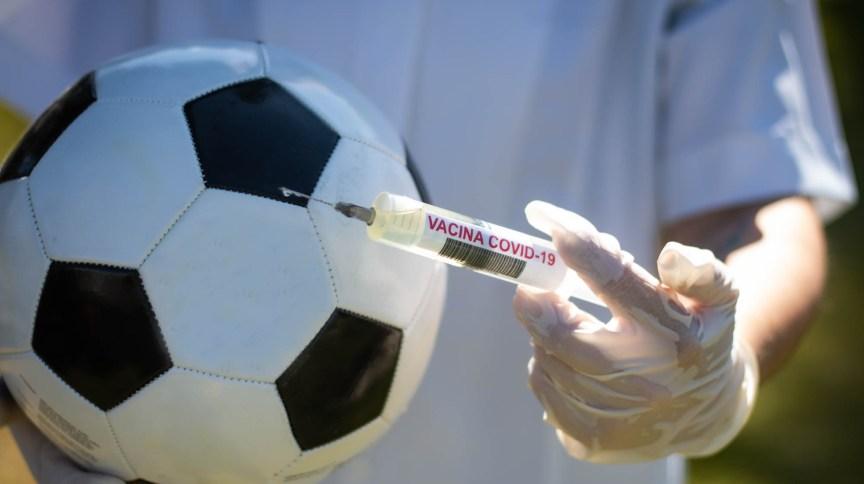 Bola de futebol ao lado de seringa e ampola em alusão à vacina para Covid-19