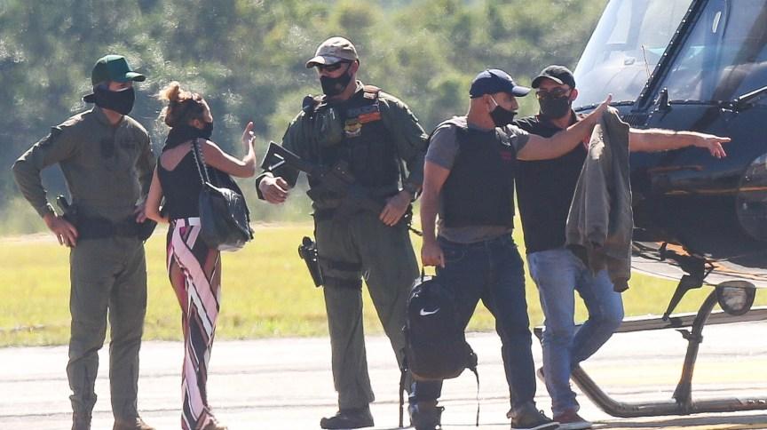 Cercado por policiais, Fabrício Queiroz (2º à direita), desembarca de helicóptero no Aeroporto de Jacarepaguá, no Rio