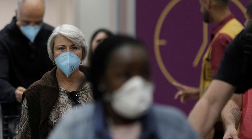 Passageiros usam máscaras ao desembarcar no aeroporto do Galeão, no Rio de Janeiro