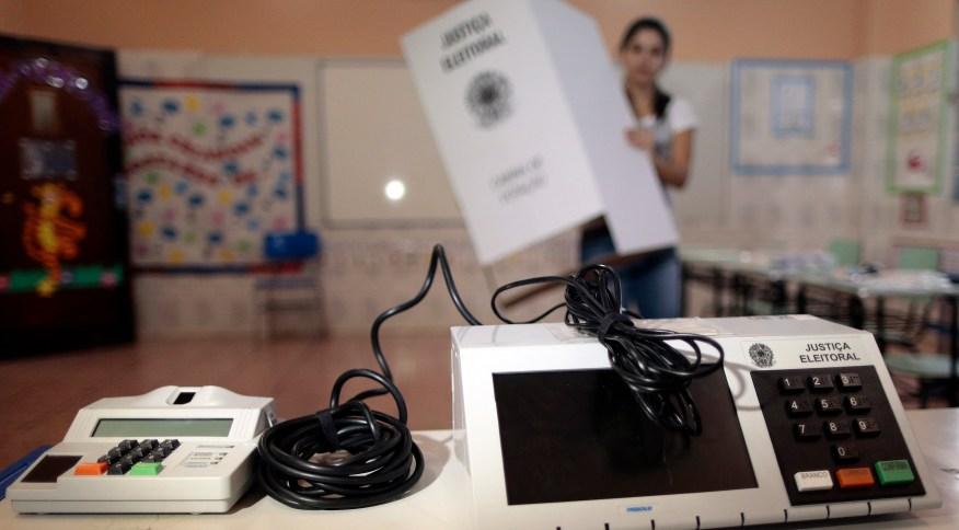 Funcionária da Justiça Eleitoral instala urna eletrônica em local de votação em escola de Brasília