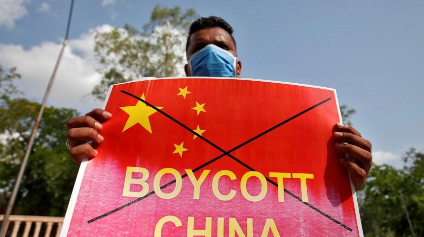 Manifestante na Índia segura cartaz defendendo boicotes contra a China