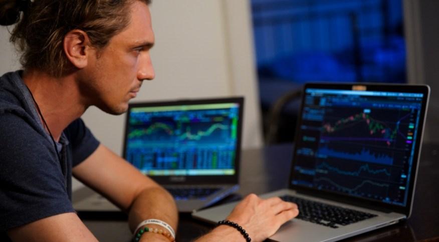 Homem acompanha ativos em terminal de investimentos